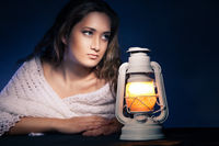 beautiful woman sitting with lantern over dark