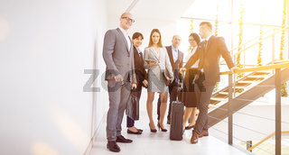 Business Team Standing Together On Corridor In Office