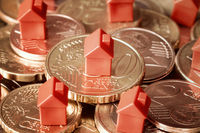 Close-up of mini houses resting on coins pile