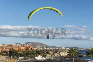 Against the background of the sky and the coastline, the paraglider descends