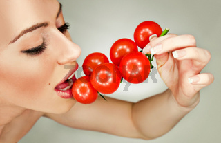 Closeup portrait of a happy beautiful girl eating tomatoes