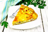 Quiche with pumpkin and bacon in white plate on table
