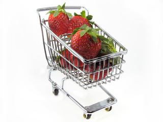 Fresh strawberries in chrome shopping cart isolated on white background