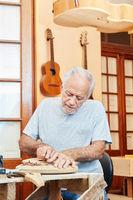Alter Gitarrenbauer arbeitet in der Werkstatt