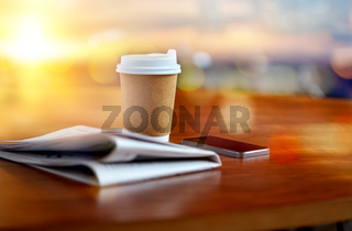 coffee cup, smartphone and newspaper on table