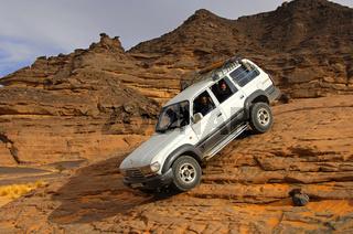 Geländefahrzeug mit Touristen passiert eine steile Felspassage
