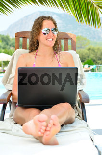 beautiful woman is sitting on wooden chair near thr pool with laptop
