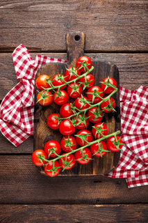 Fresh cherry tomatoes on twigs on wooden table, top view