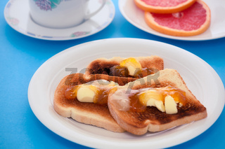 French toast with sliced orange fruit on blue tablecloth