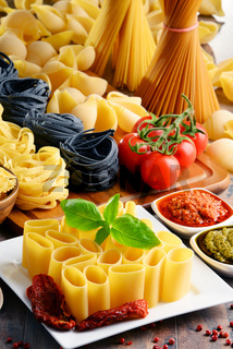 Composition with different sorts of pasta on kitchen table.