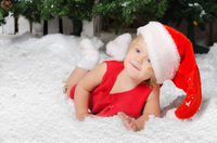 smiling little girl in santa costume on snow