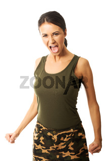 Woman in military clothes showing her agressivity by screaming and making fists