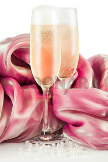 Frosted glasses of cold champagne with silk decor and white pearls