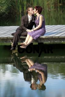ein verliebtes Paar auf einem Steg am See