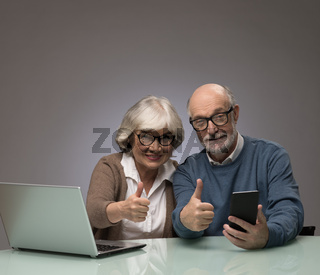 Senior couple with laptop and smartphone