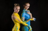 Two nude women covered with blue and yellow colors