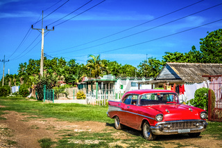 HDR - Roter amerikanischer Oldtimer parkt vor einem Haus im Landesinneren von Santa Clara Kuba - Ser