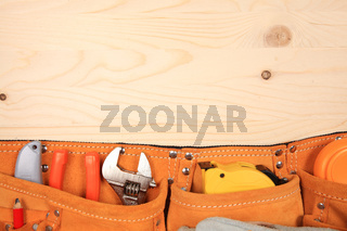 Suede belt with set of working tools on wooden background