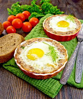 Tartlet meat with egg in pan on dark board