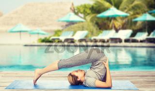 woman making yoga in plow pose on mat