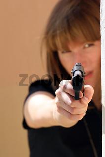 Frau zielt mit Pistole