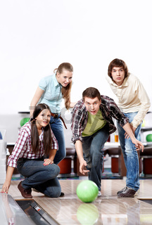 The youth observes as the young man throws a sphere for bowling