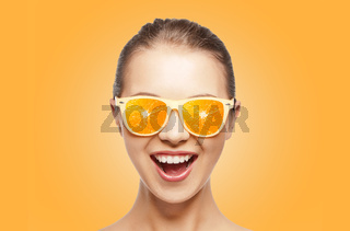 happy teenage girl in sunglasses with oranges