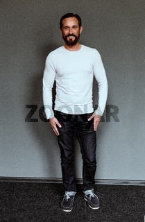 Full length portrait of mid aged smiling beardy actor.