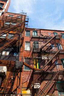 The typical american fire escape ladder zigzagging across the face and windows.