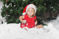 smiling girl in santa costume sits on snow
