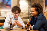 men with smartphone drinking beer at bar or pub
