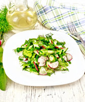 Salad of radish and sorrel with oil in plate on board