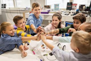 happy children making high five at robotics school