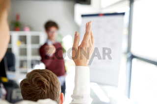 woman raising hand at presentation in office