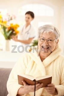 Happy elderly woman reading book
