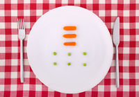 Tablecloth with fork, knife, six peas and three ca