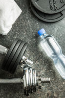 Dumbbell, bottle of water and white towel.