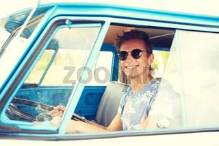 smiling young hippie man driving minivan car