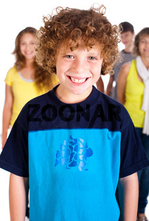 Smiling kid in focus with family posing in the background