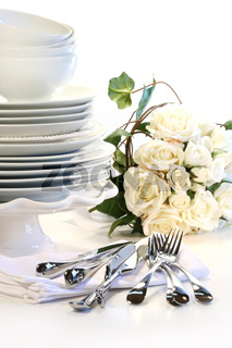 White plates stacked with utencils and roses