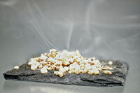 Incense with smoke on a black stone slab
