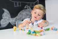 Portrait of cute toddler boy playing with toys at the desk at home.