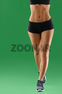 Beautiful sportswoman posing on green background
