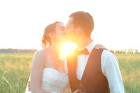 Young just married couple kissing each other by sunset