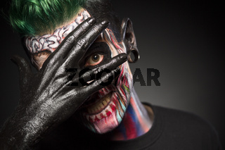 Man with skeleton make up, covering face with black painted hand.