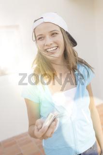 Junge lachende Frau haelt eine Kamera in der Hand