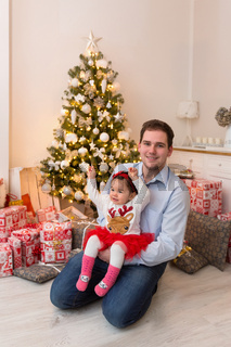 Young happy family in front of a Christmas tree
