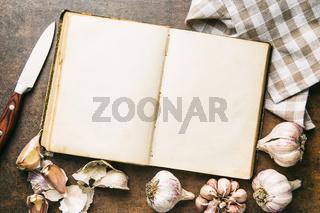 Blank cookbook and garlic.