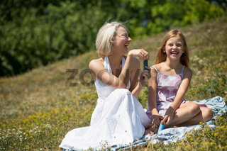 Laughing mother and daughter sitting on blanket outdoors.
