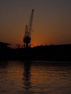 Silhouette eines Krans im Hafen von Lübeck, Deutschland, bei Sonnenuntergang